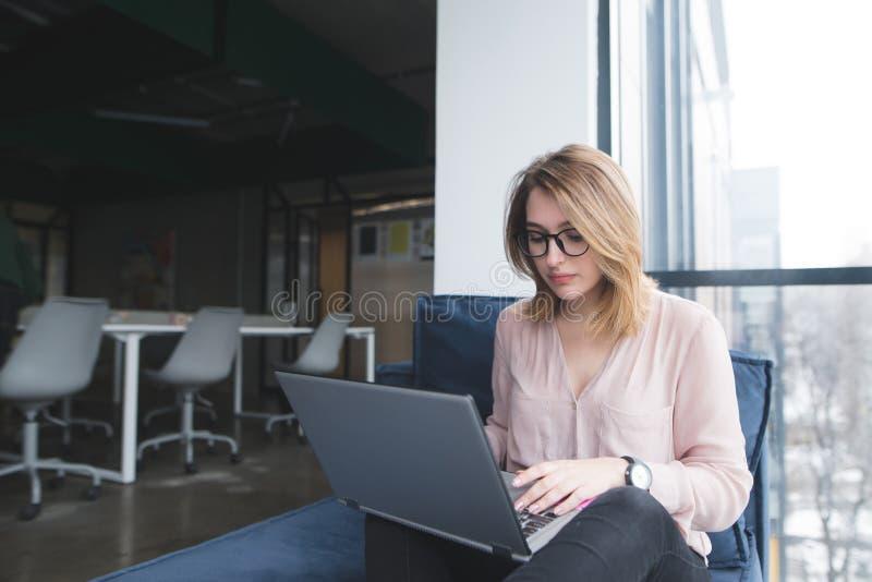 Dziewczyna pracuje na laptopie na kanapie w biurze Nowożytny obieg wewnątrz Praca w coworking zdjęcie royalty free