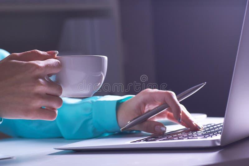 Dziewczyna pracuje póżno w ciemnym biurze z laptopem Młoda bizneswoman dziewczyna w biurze W górę fotografii a obrazy royalty free