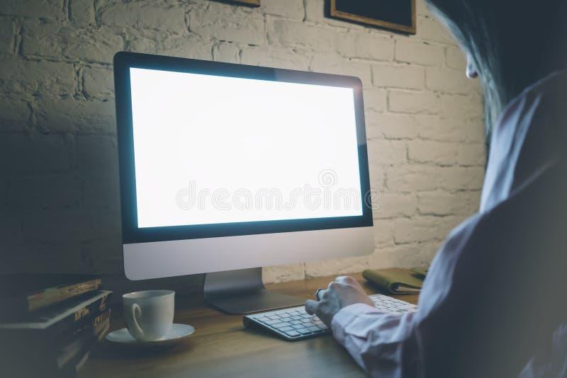 On dziewczyna pracuje za komputerową klawiaturą i patrzeje pustego monitoru z błękitnym ekranem na twój drewnianym stole przeciw  fotografia stock