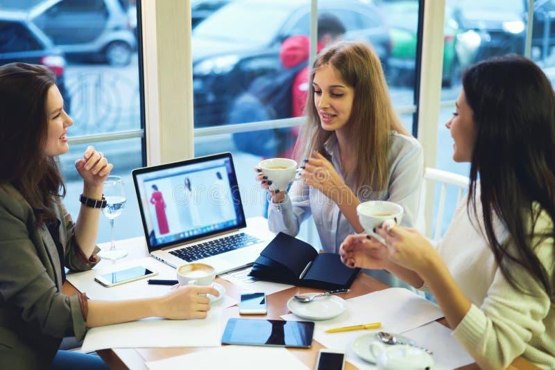 Dziewczyna projektantów ubrania pracuje wpólnie łączyli wifi surfować internet patrzeje dla eleganckiego odziewają obrazy stock