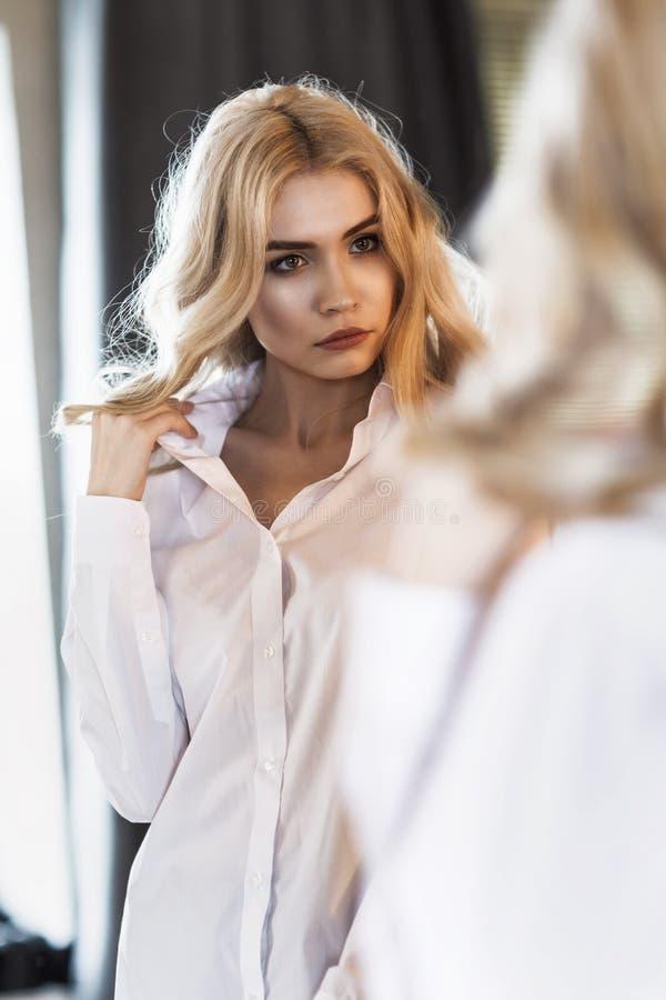Dziewczyna prostuje białą koszula przed lustrem obrazy stock