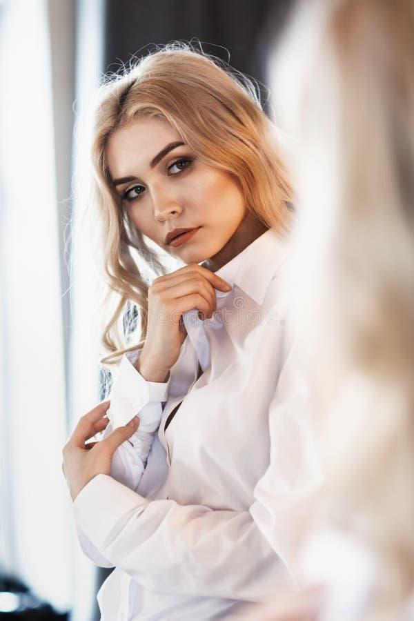 Dziewczyna prostuje odzieżowego przed lustrem fotografia stock