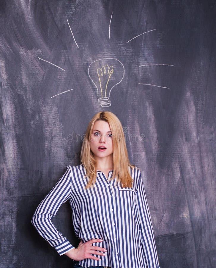 Dziewczyna przed chalkboard z żarówką rysującą nad jej głowa fotografia royalty free