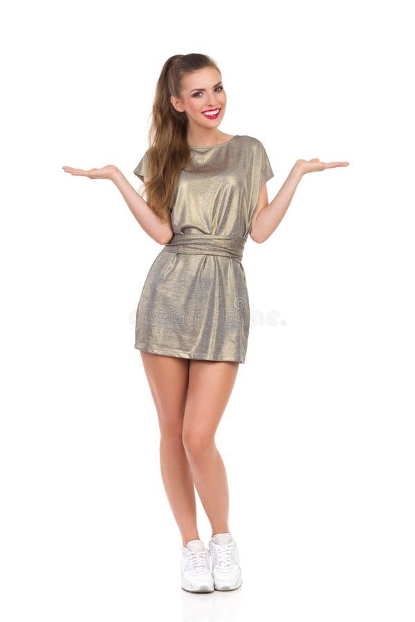 Dziewczyna Przedstawia ProductCheerful młodej kobiety stoi z rękami podnosić w złocistej mini sukni i białych sneakers W Mini suk obraz stock