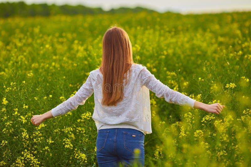 Dziewczyna przy żółtą rapeseed łąką zdjęcia royalty free