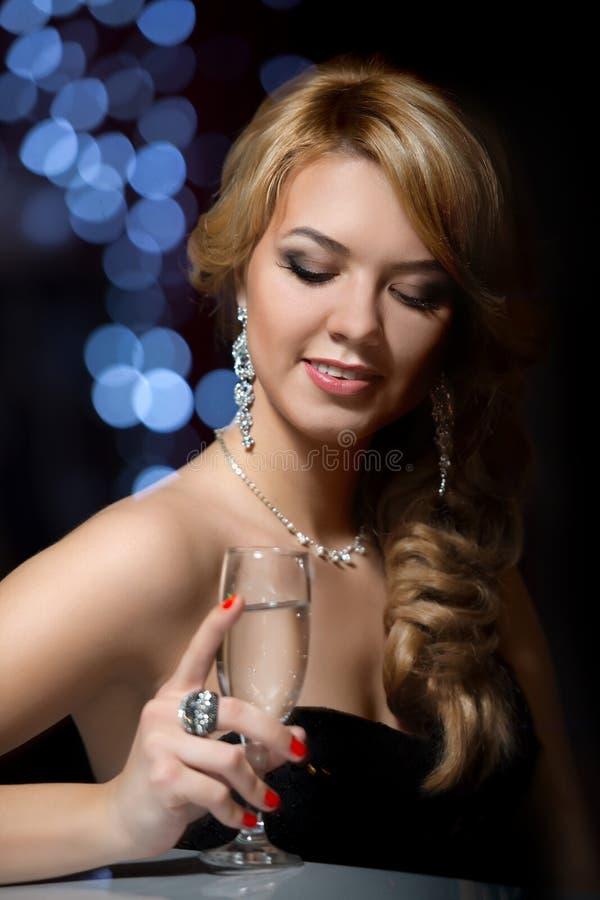 Dziewczyna przy barem z szkłem szampan obrazy stock