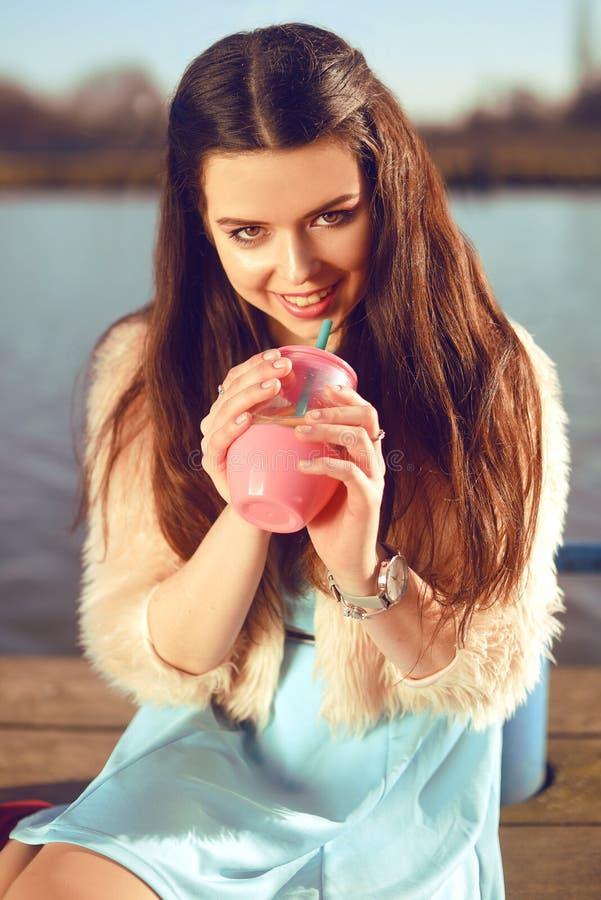 Dziewczyna przy gorącym słonecznego dnia napoju lemonad Lato klimaty Dziewczyna z mody czerni suknią, różowy futerkowy żakiet Pię obrazy royalty free