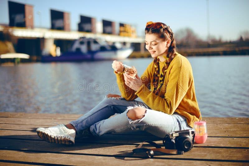 Dziewczyna przy gorącym słonecznym dniem je lody Lato klimaty Dziewczyna z moda żółtymi okularami przeciwsłonecznymi i ubierająca zdjęcie royalty free