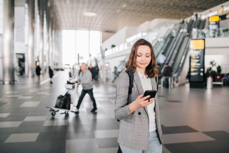 Dziewczyna przy lotniskiem, patrzeje jej smartphone zdjęcie stock
