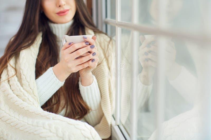 Dziewczyna przy okno z filiżanką w zimie zdjęcie royalty free