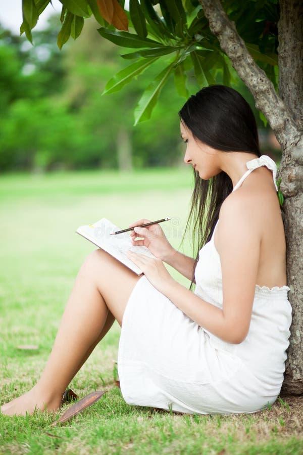 Dziewczyna przy parkiem pisze w jej osobistym dzienniczku zdjęcie royalty free