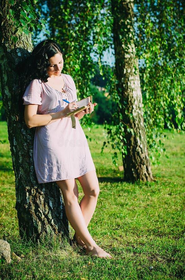 Dziewczyna przy parkiem pisze w jej osobistym dzienniczku obrazy stock