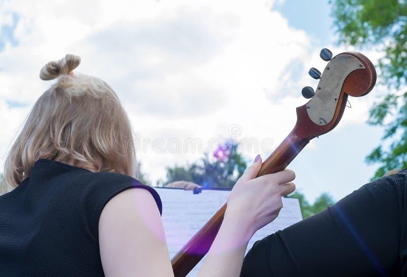 Dziewczyna przy ulicznym koncertem outdoors bawić się kontrabas, instrument muzyczny obrazy stock