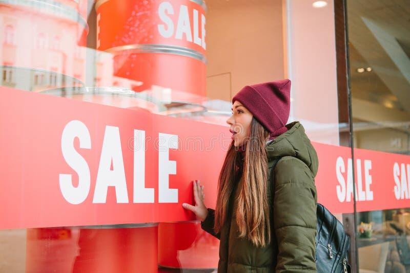 Dziewczyna przy witryną sklepową z sprzedażą fotografia royalty free