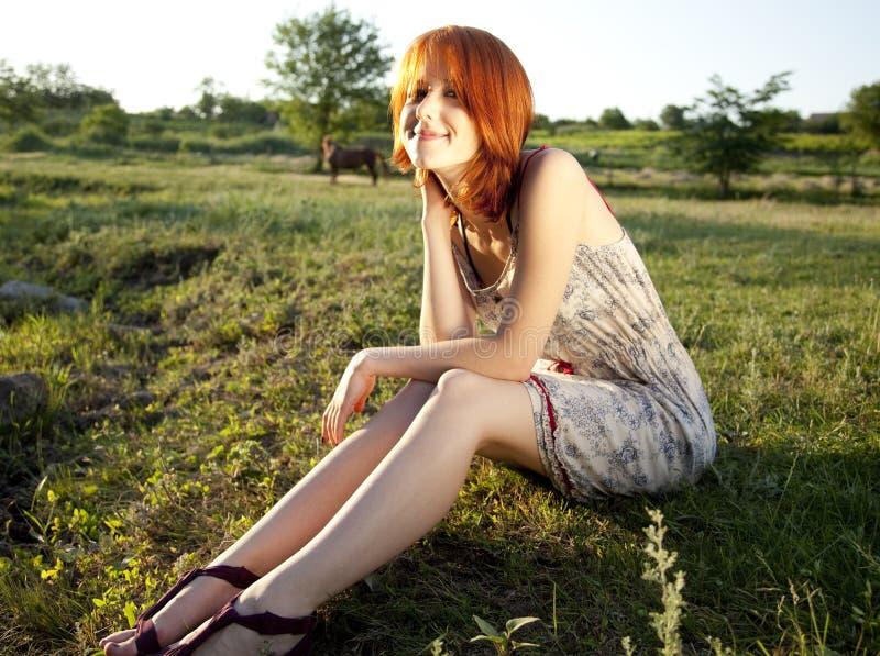 Dziewczyna przy zielonej trawy polem przy zmierzchem. zdjęcia royalty free