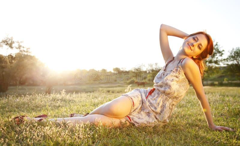 Dziewczyna przy zielonej trawy polem przy zmierzchem. obrazy stock