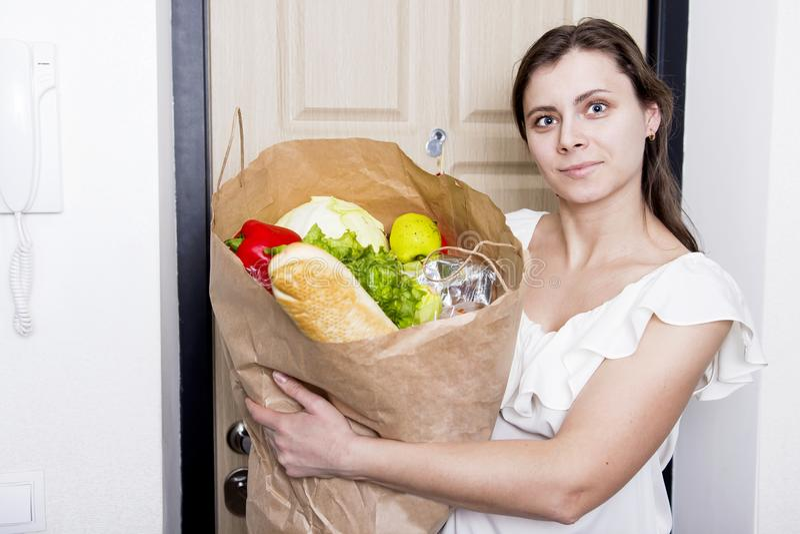 Dziewczyna przychodził do domu z pakunkiem jedzenie młoda kobieta przynosząca do domu od sklepów spożywczych warzyw Zakup produkt fotografia stock
