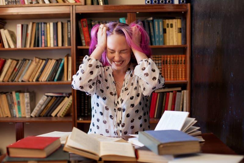 Dziewczyna przygotowywa dla egzaminu czytelnicza książka w bibliotece jest zmęczona obraz stock