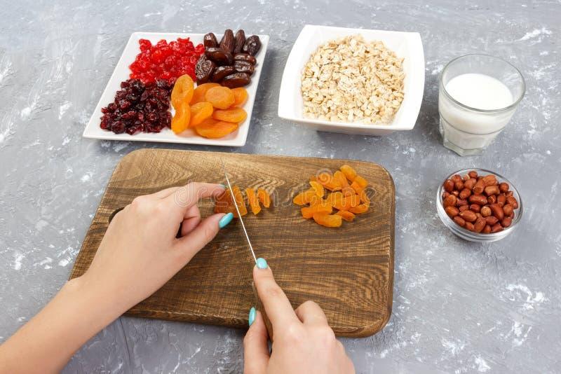 Dziewczyna przygotowywa jej śniadaniowy rozcięcie suszyć owoc w oatmeal owsiankę na tnącej desce Pożytecznie i zdrowy śniadanie o fotografia royalty free