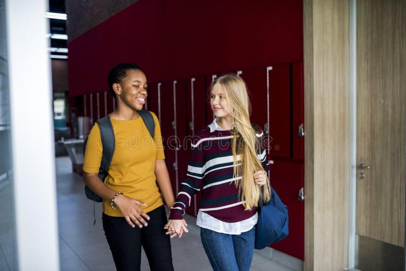 Dziewczyna przyjaciele chodzi ręki wpólnie i trzyma zdjęcia royalty free