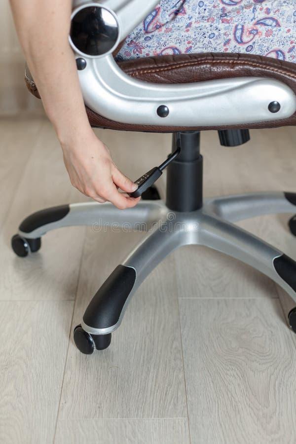 Dziewczyna przystosowywa wzrost nowy brown biurowy krzesło obraz royalty free