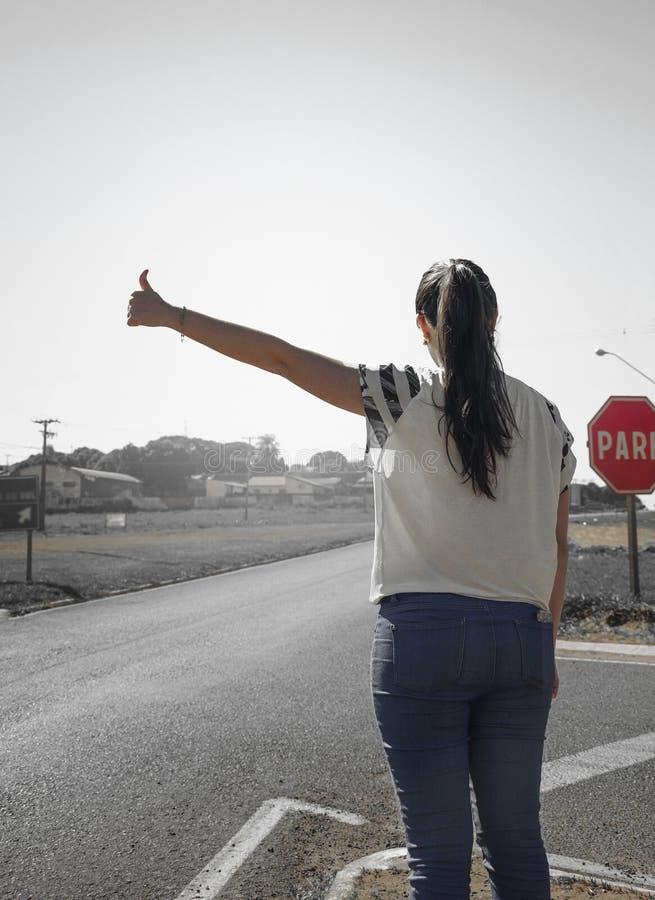 Dziewczyna pyta dla przejażdżki na poboczu autostrada obraz royalty free