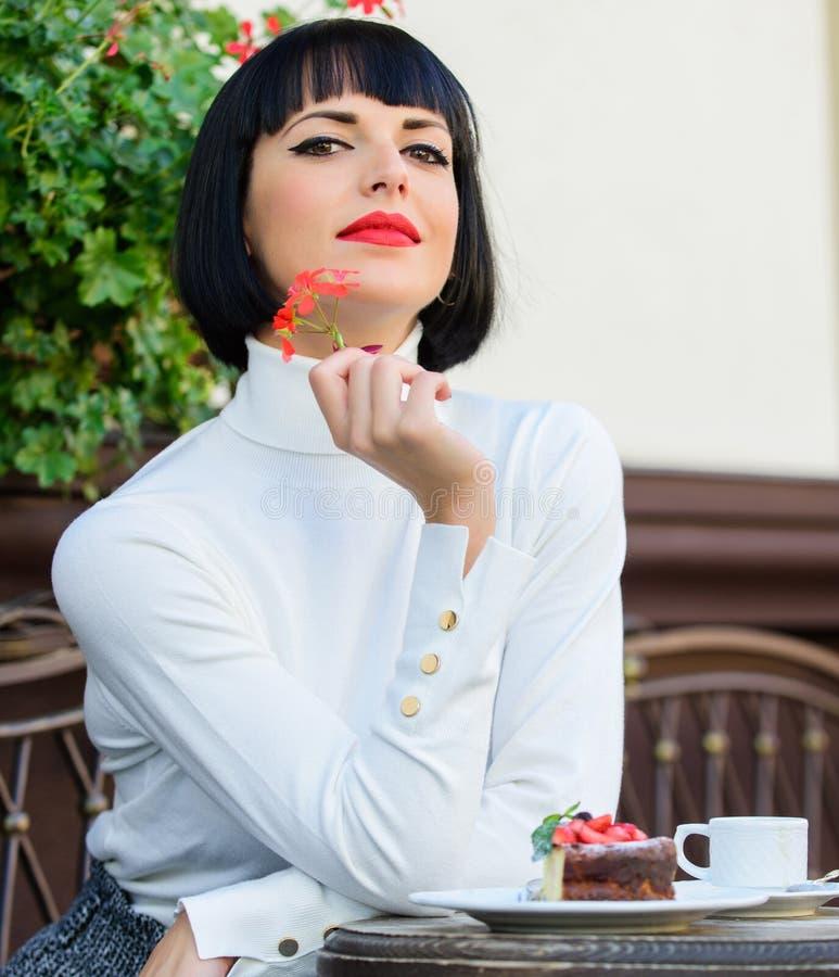 Dziewczyna relaksuje kawiarni z tortowym deserem Kobiety atrakcyjna elegancka brunetka je smakosz kawiarni tarasu tortowego tło s obrazy royalty free