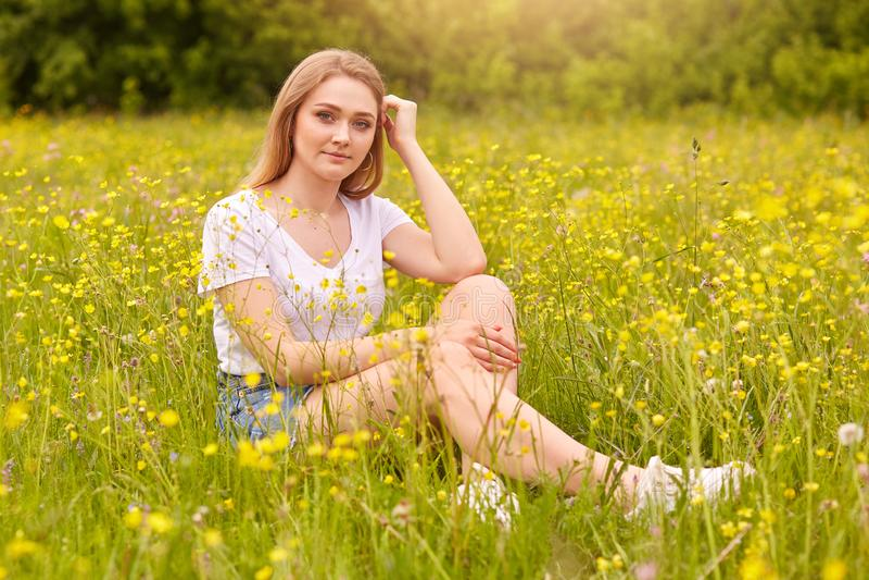 Dziewczyna relaksuje w ??ce i cieszy si? letniego dzie?, blondynki m?odej kobiety pi?kny obsiadanie na trawie otaczaj?cej z pole  fotografia royalty free