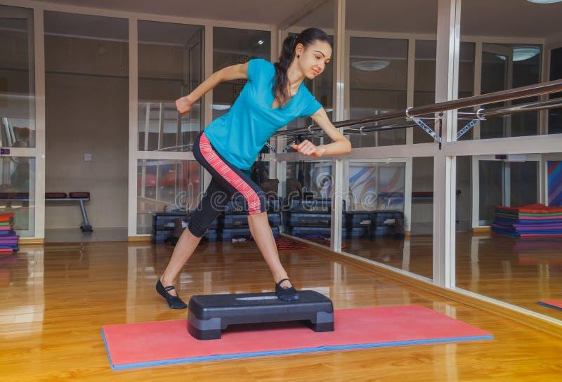 Dziewczyna robi ćwiczeniom krok platforma w gym, Zdrowy styl życia obraz stock