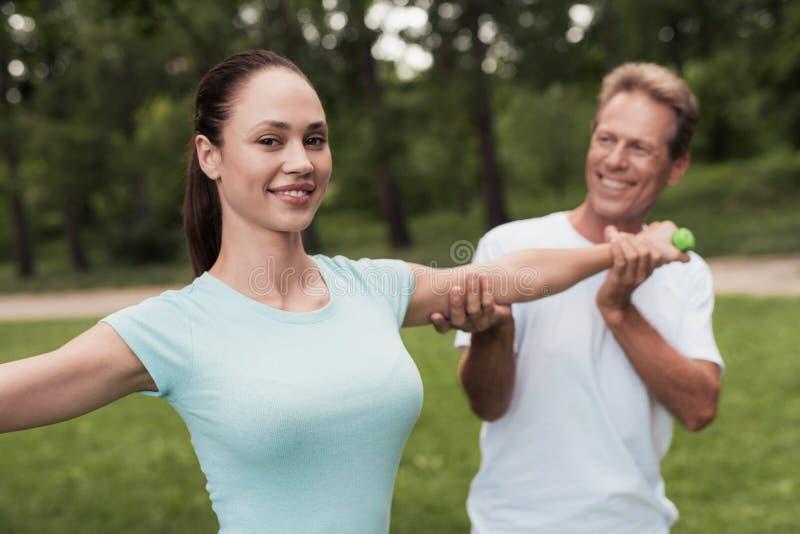 Dziewczyna robi ćwiczeniom z dumbbells w parku Mężczyzna pomaga ona Są uśmiechnięci zdjęcie stock