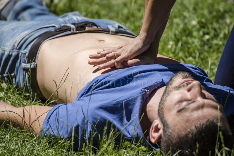 Dziewczyna robi cardiopulmonary resuscitation nieświadomie facet po ataka serca zdjęcia royalty free
