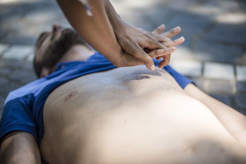 Dziewczyna robi cardiopulmonary resuscitation nieświadomie facet po ataka serca zdjęcia stock