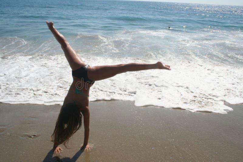 Dziewczyna Robi Cartwheel na plaży fotografia stock