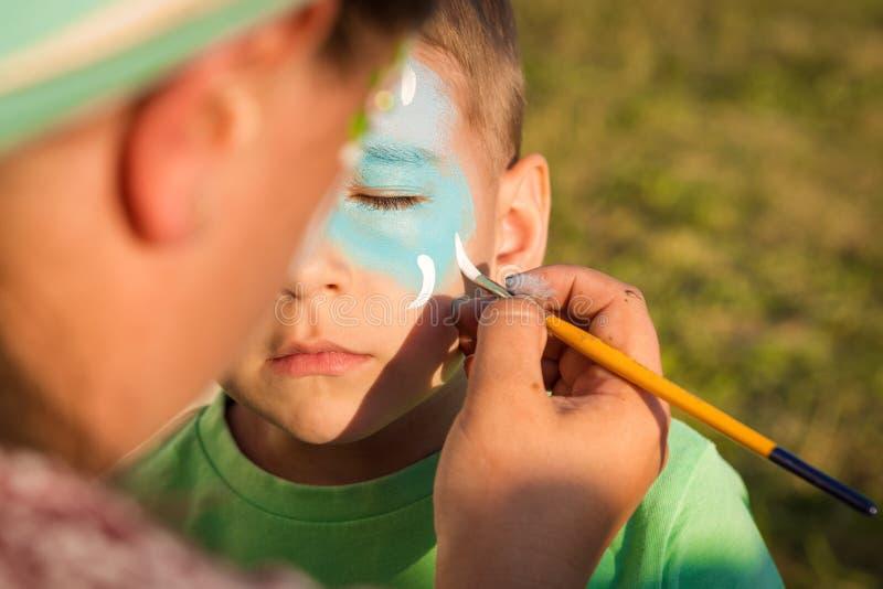 Dziewczyna robi greasepaint na dziecko twarzy zdjęcia royalty free