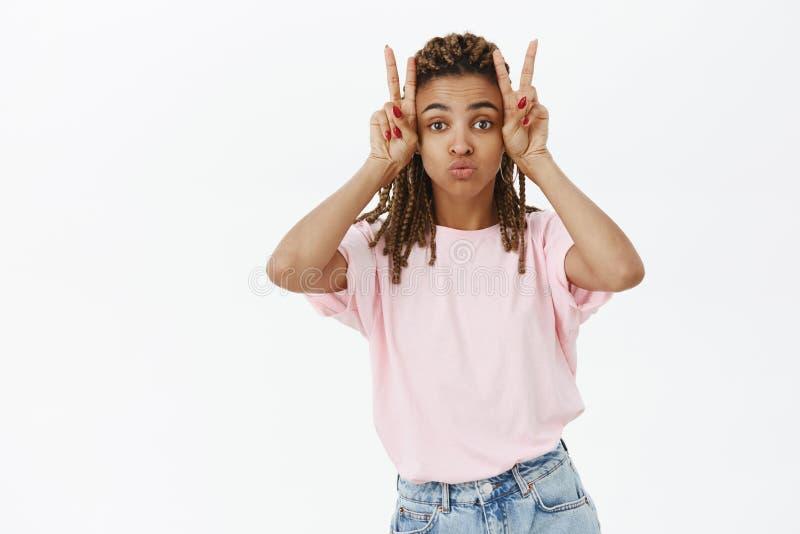 Dziewczyna robi niemądrej twarzy podczas gdy pozujący przeciw popielatej ścianie Portret czarować kobiecej i eleganckiej amerykan obraz stock