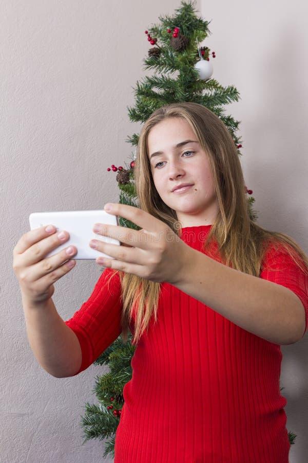 Dziewczyna robi selfie blisko nowego roku drzewa zdjęcia stock