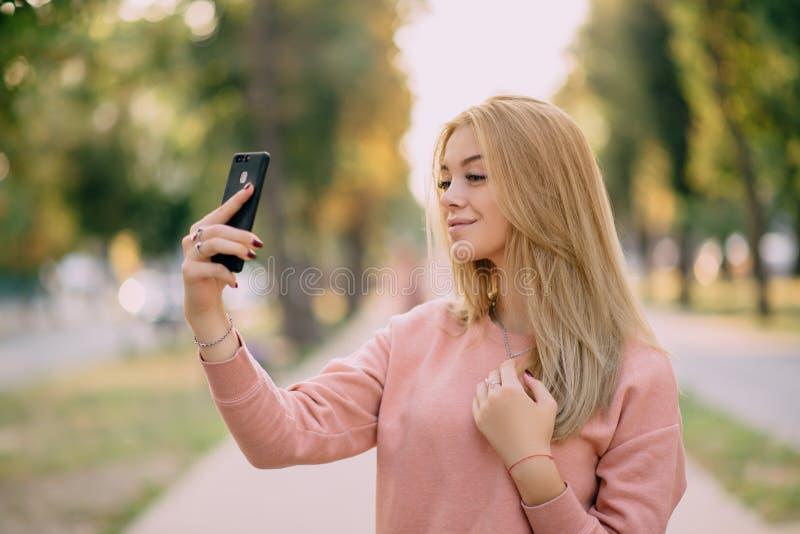 Dziewczyna robi selfie na grodzkiej alei obrazy stock