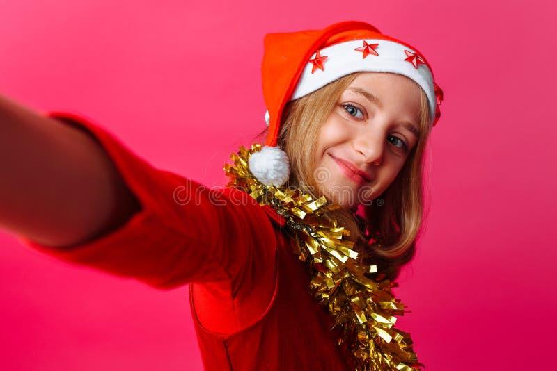 Dziewczyna robi selfie w kapeluszu Święty Mikołaj i świecidełko dalej zdjęcie royalty free