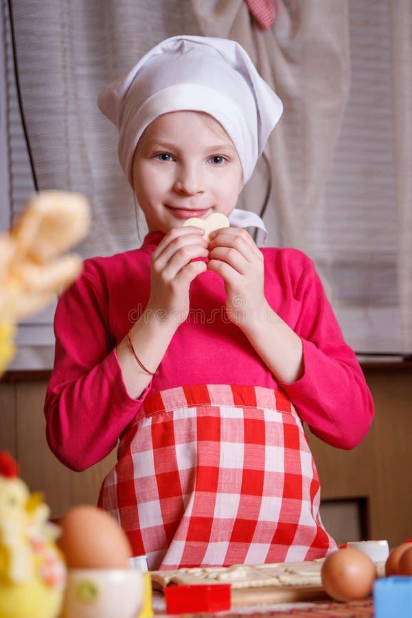 Dziewczyna robi sercowatym ciastkom zdjęcie stock