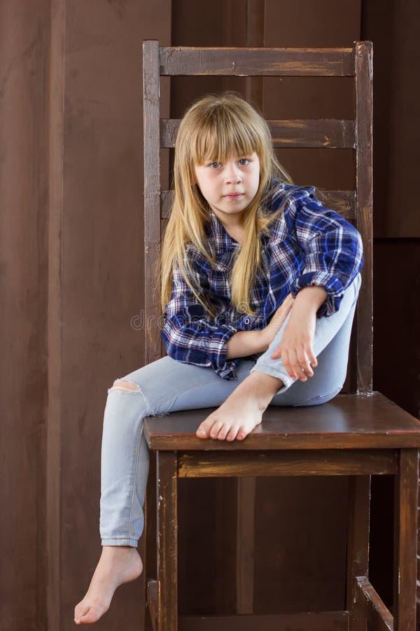 Dziewczyna 6 rok siedzi na wysokim krześle obraz royalty free