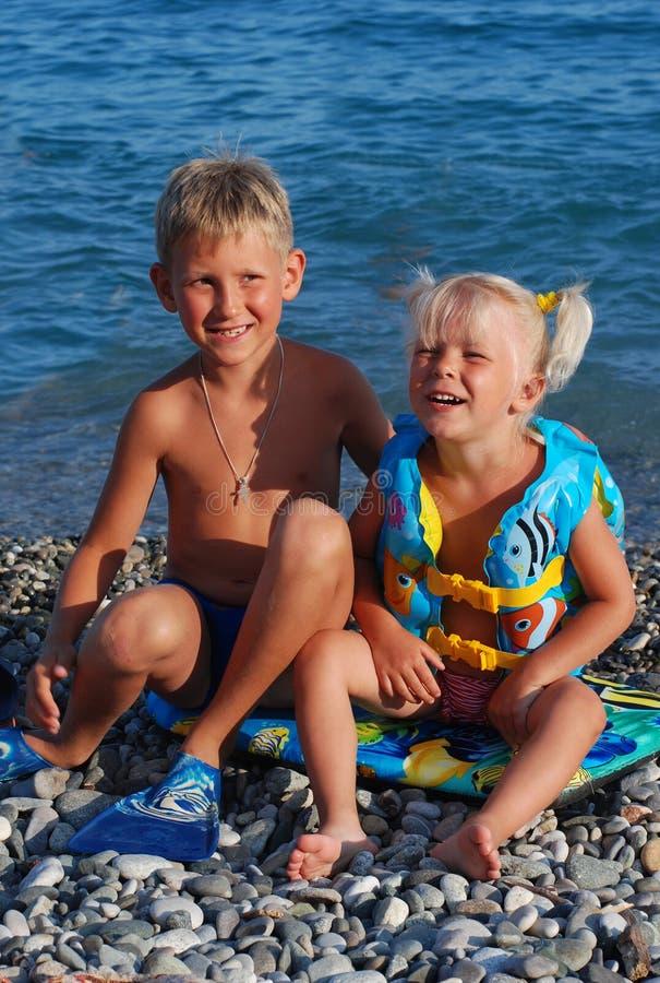 Dziewczyna 3 roku blondynka i jej starszy brat na morzu, obrazy royalty free