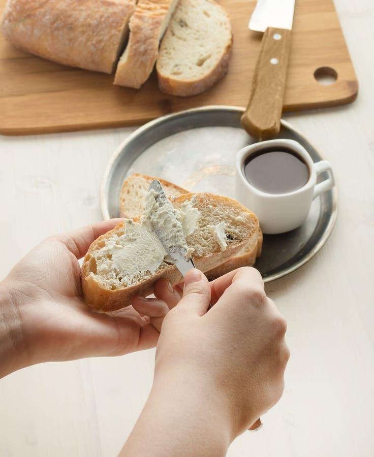 Dziewczyna rozprzestrzenia miękkich twaróg na chlebie Kanapka świeży ciabatta z masłem wyśmienite śniadanie zdjęcie stock