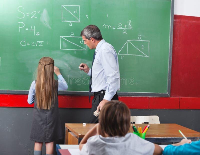Dziewczyna Rozwiązuje Mathematics Z Na Pokładzie nauczyciela zdjęcie royalty free