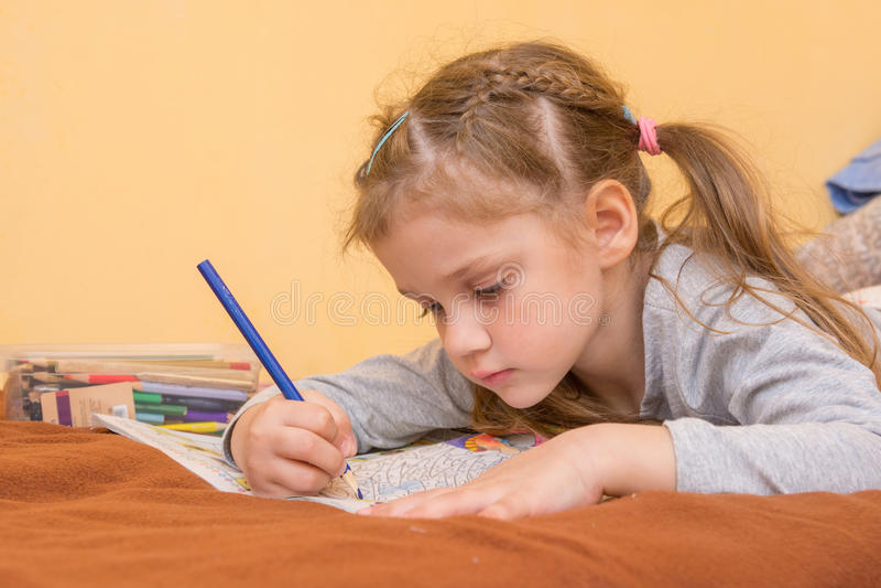 Dziewczyna rysuje ciężkiego lying on the beach na jego żołądku z ołówkiem na papierze obraz stock