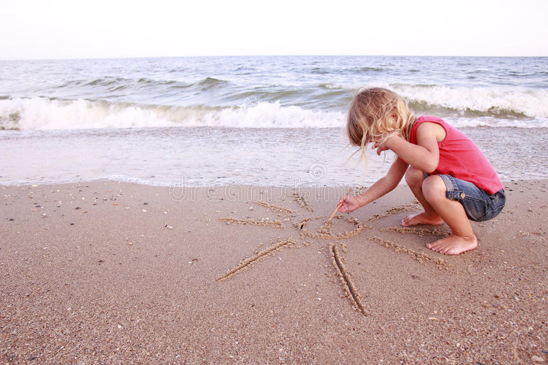 Dziewczyna rysuje słońce w piasku na plaży