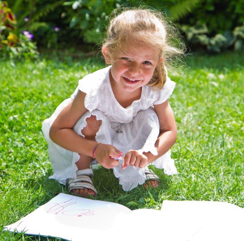 Dziewczyna rysunek na książce na trawie obrazy royalty free