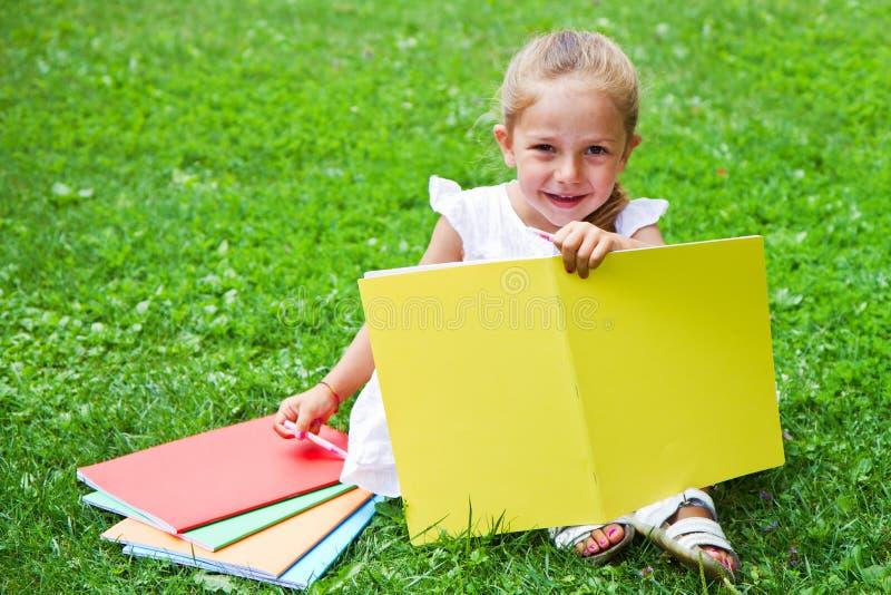 Dziewczyna rysunek na książce na trawie zdjęcie stock