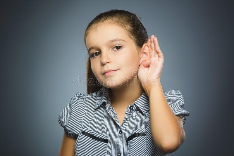 dziewczyna słucha dziecka przesłuchanie coś, ręka uszaty gest na popielatym tle zdjęcie stock