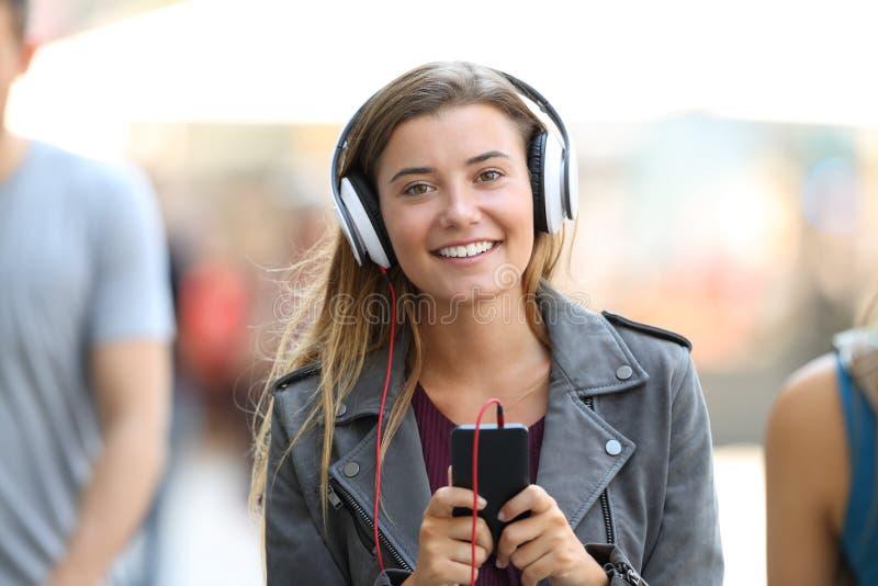 Dziewczyna słucha muzyka na telefonie i patrzeje ciebie obrazy stock