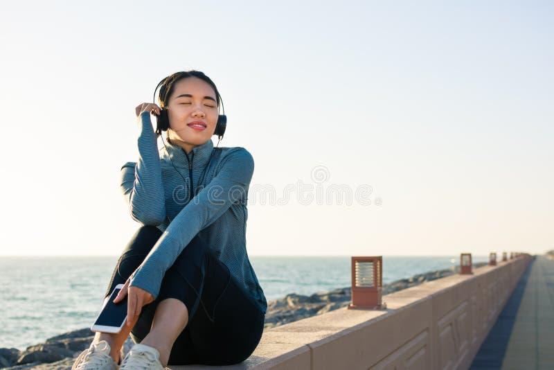 Dziewczyna słucha muzyka nadmorski i cieszy się słonecznego dzień fotografia royalty free